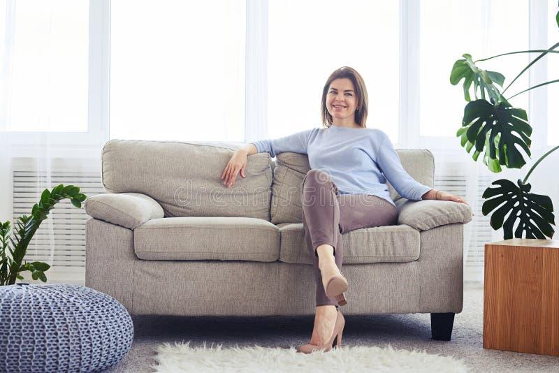 Donna in vestiti alla moda che si siedono sul sofà in ro luminoso di vita fotografie stock libere da diritti