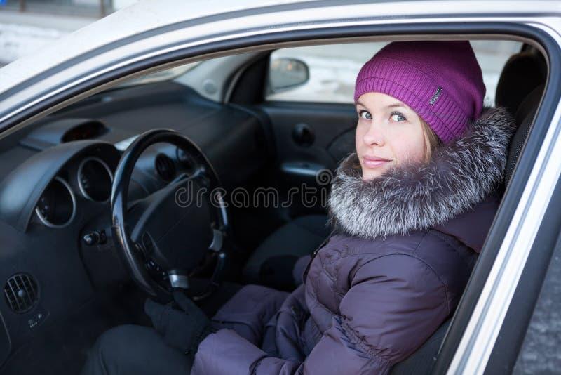 Donna in vestiti di inverno che si siedono in automobile fotografia stock libera da diritti