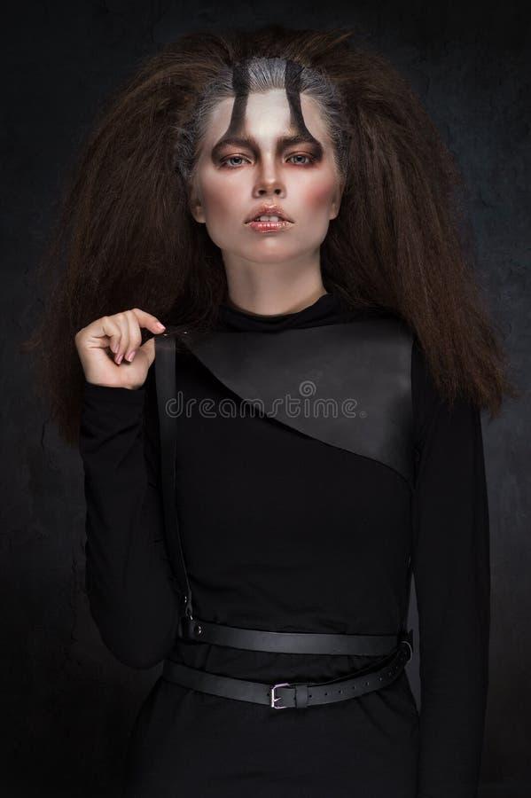 Donna in vestiti neri con trucco scuro espressivo fotografie stock