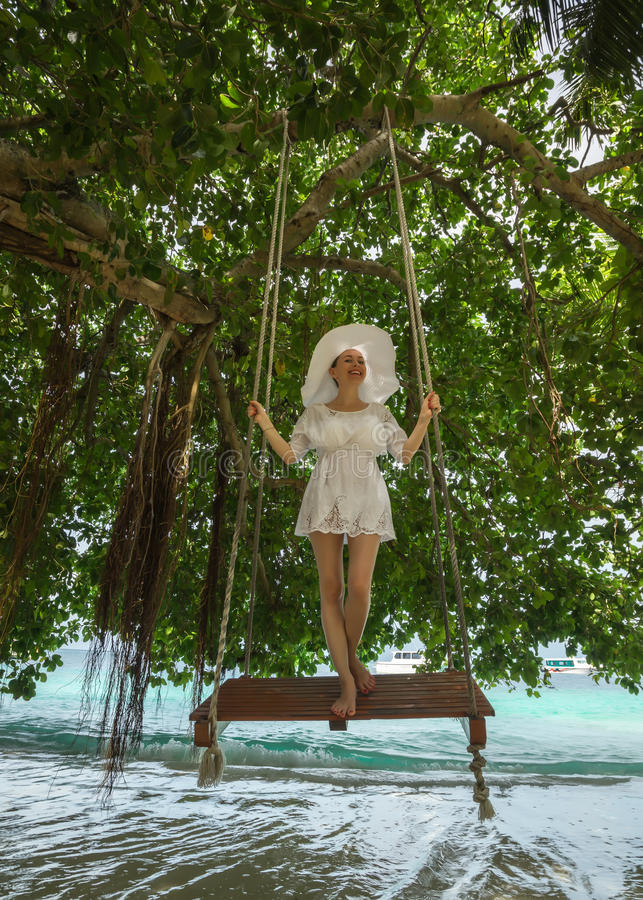 Donna in vestito bianco che oscilla alla spiaggia tropicale immagini stock