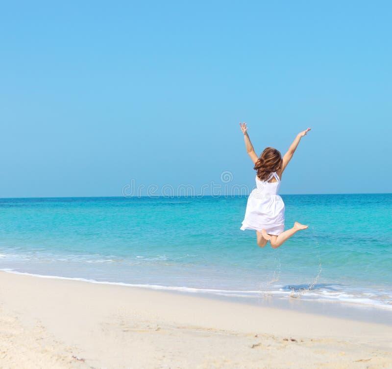Donna in vestito bianco che salta sulla spiaggia fotografie stock libere da diritti