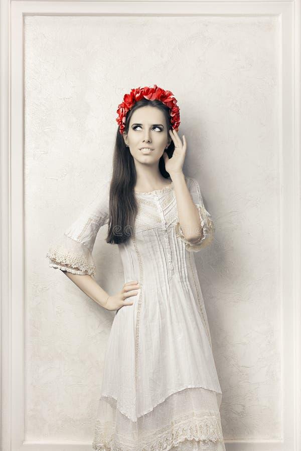 Donna in vestito bianco da stile d'annata e corona floreale fotografia stock