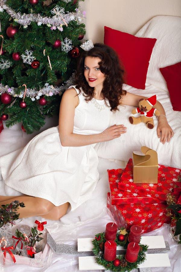 Donna in vestito bianco festivo fra la decorazione di Natale fotografia stock