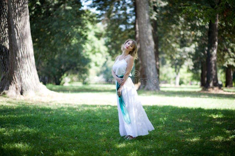 Donna in vestito bianco in parco verde Concetto di Eco immagini stock libere da diritti
