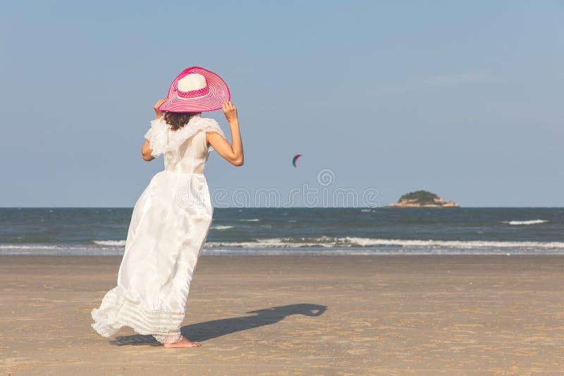 Donna in vestito bianco sulla spiaggia immagini stock libere da diritti