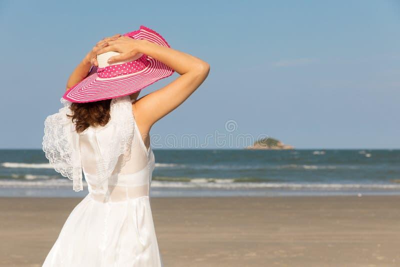 Donna in vestito bianco sulla spiaggia immagini stock