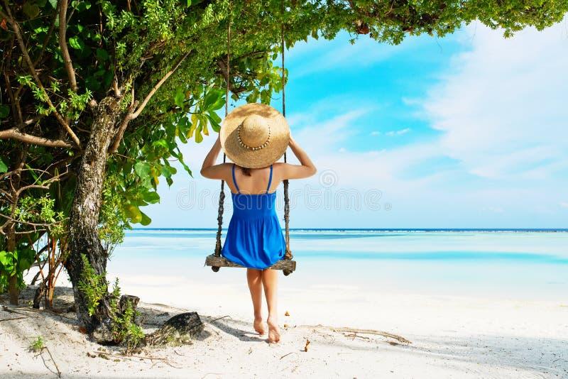 Donna in vestito blu che oscilla alla spiaggia immagini stock libere da diritti