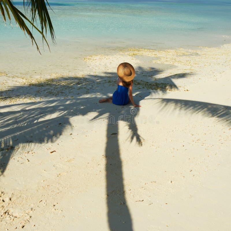 Donna in vestito blu su una spiaggia alle Maldive immagini stock