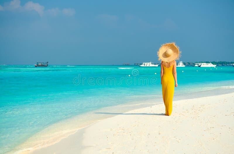 Donna in vestito che cammina sulla spiaggia tropicale immagini stock