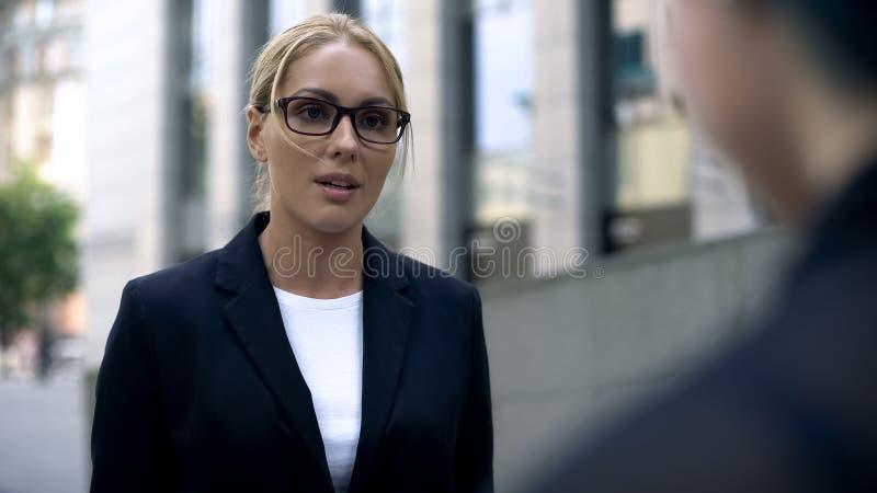 Donna in vestito che parla con il cliente, esperto nella sua materia, interprete fotografia stock libera da diritti