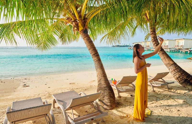 Donna in vestito che prende selfie sulla spiaggia tropicale fotografie stock