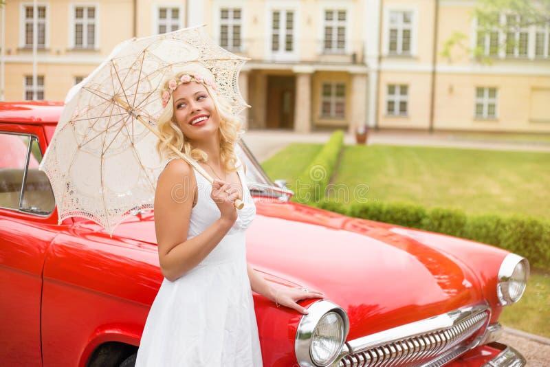 Donna in vestito che sta accanto alla retro automobile rossa fotografia stock