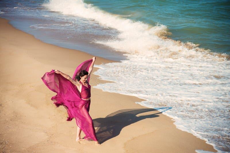 Donna in vestito cremisi aerato sulla spiaggia fotografia stock
