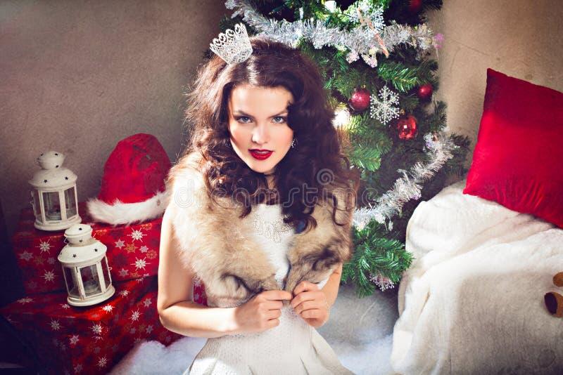 Donna in vestito d'annata festivo davanti all'albero di Natale immagine stock libera da diritti