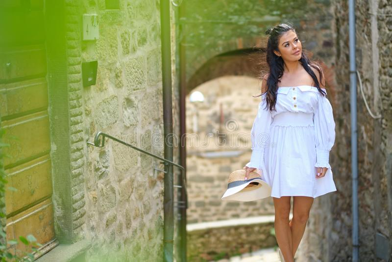 Donna in vestito da estate che cammina e che esegue sorridere allegro e allegro in Toscana, Italia fotografie stock