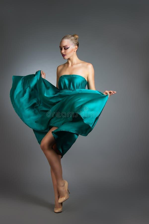 Donna in vestito di seta che ondeggia sul vento Panno volante e d'ondeggiamento dell'abito sopra fondo grigio fotografie stock