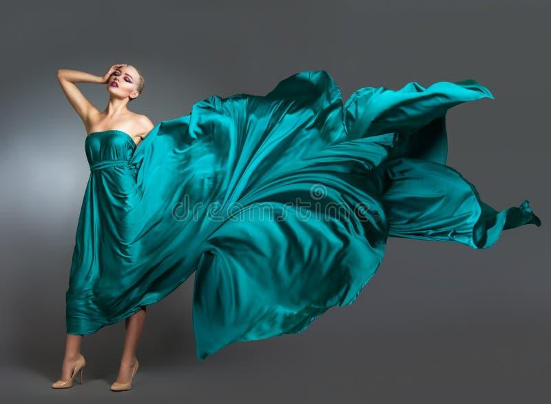 Donna in vestito di seta che ondeggia sul vento Panno volante e d'ondeggiamento dell'abito sopra fondo grigio immagine stock