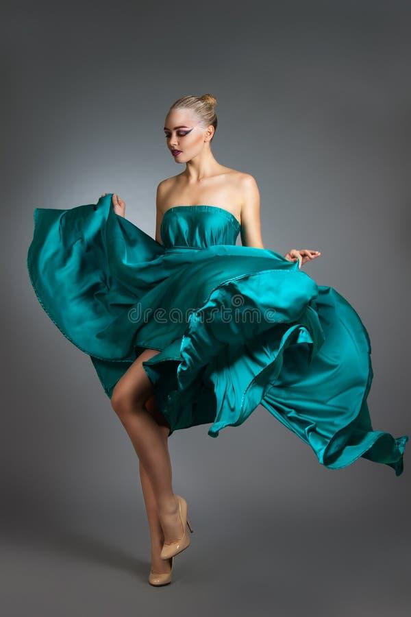 Donna in vestito di seta che ondeggia sul vento Panno volante e d'ondeggiamento dell'abito sopra fondo grigio fotografia stock