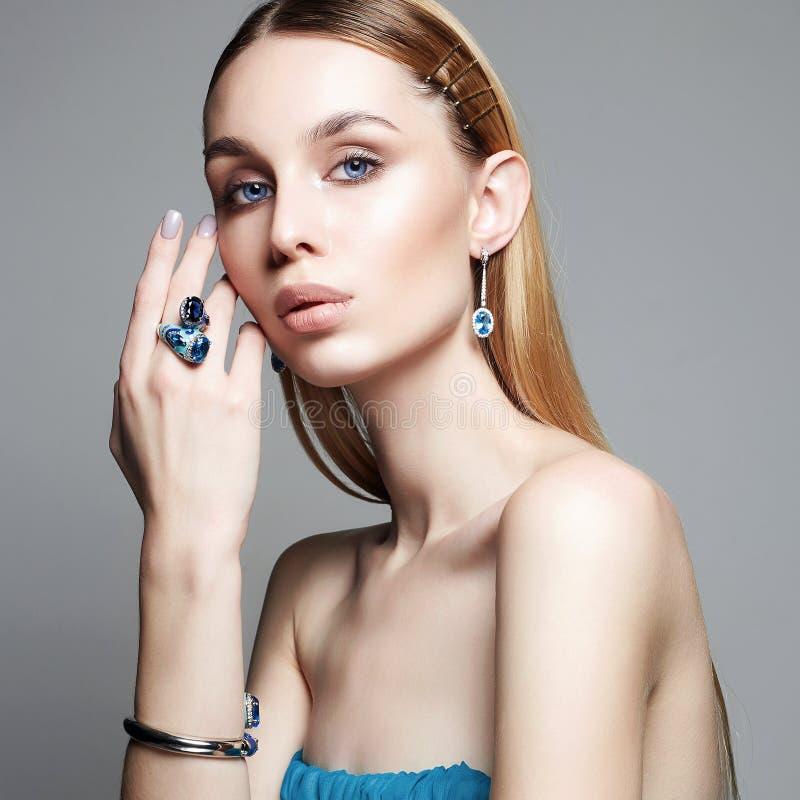 Donna in vestito e gioielli blu gioielli sulla bella ragazza immagini stock