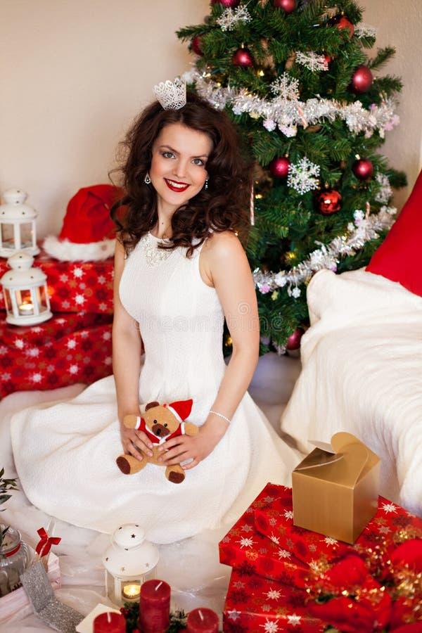 Donna in vestito festivo davanti all'albero di Natale immagini stock libere da diritti
