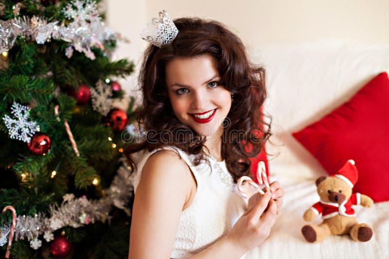 Donna in vestito festivo vicino all'albero di Natale immagini stock libere da diritti