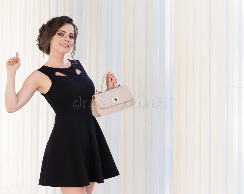 Donna in vestito nero, borsa beige, fondo bianco, sorriso fotografie stock libere da diritti