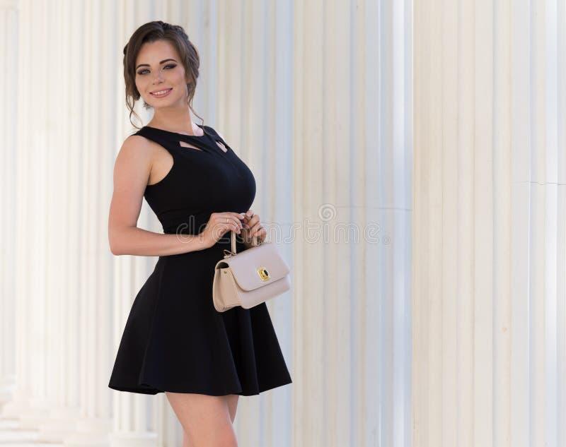 Donna in vestito nero, borsa beige, fondo bianco, sorriso fotografia stock libera da diritti