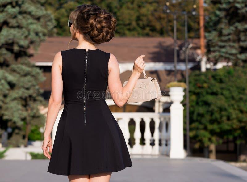 Donna in vestito nero, borsa beige, fondo della città, posteriore immagini stock libere da diritti