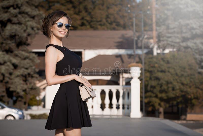 Donna in vestito nero, borsa beige, fondo della città, sorriso, sole immagini stock