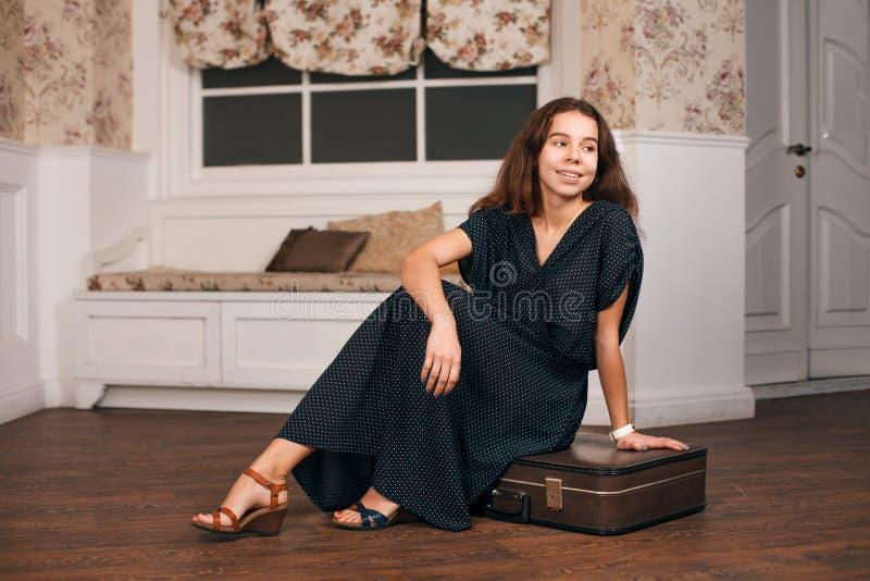 Donna in vestito nero che si siede sulla sua valigia fotografia stock libera da diritti