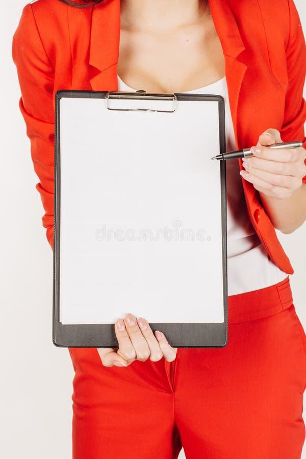 Donna in vestito rosso che mostra con la pagina in bianco della lavagna per appunti Isolante immagine stock libera da diritti