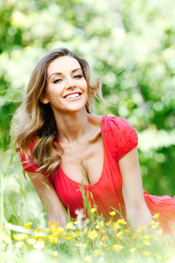 Donna in vestito rosso che si siede sull'erba fotografia stock