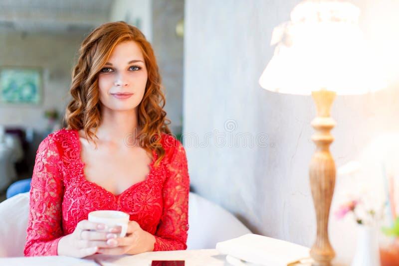 Donna in vestito rosso che si siede in un caffè con il suo telefono cellulare immagini stock libere da diritti