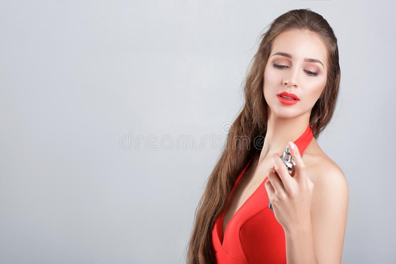 Donna in vestito rosso con profumo fotografie stock libere da diritti
