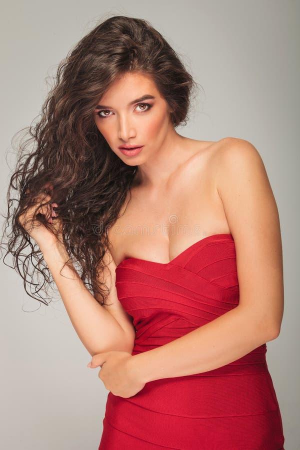 Donna in vestito rosso sexy che posa nello studio fotografia stock