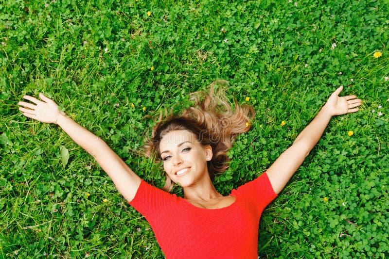 Donna in vestito rosso su erba fotografia stock