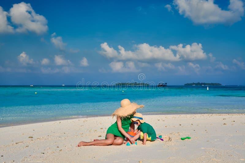 Donna in vestito verde con il ragazzo di tre anni sulla spiaggia fotografie stock