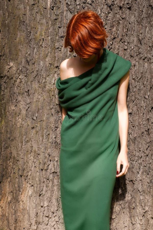 Donna in vestito verde contro la quercia gigante fotografie stock