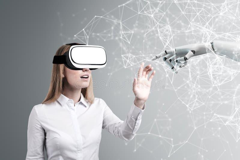 Donna in vetri di VR, mano del robot fotografie stock
