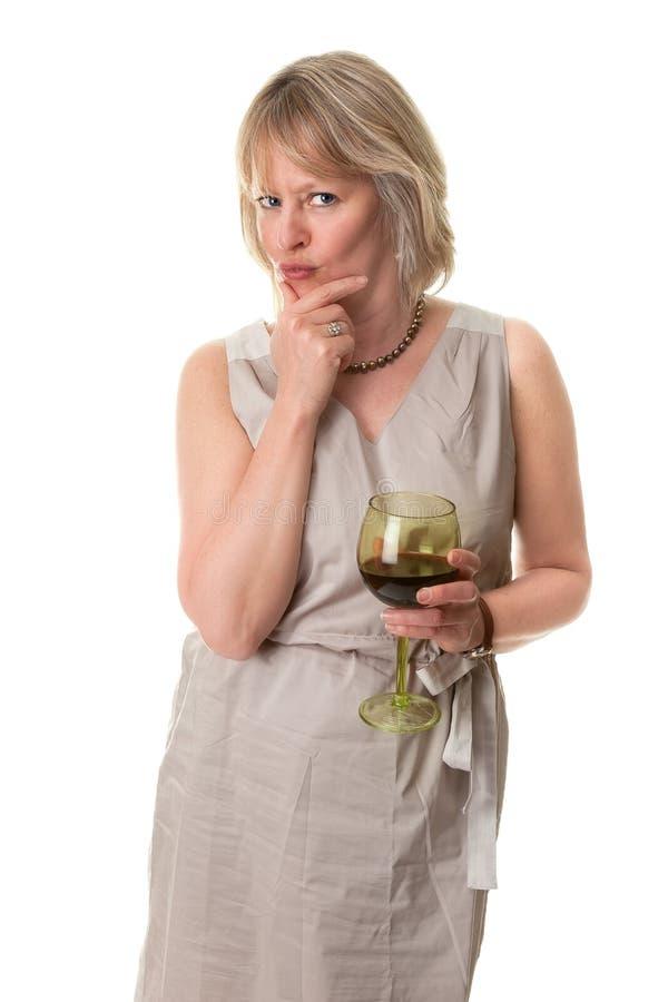 Donna in vetro di vino della holding di pensiero fotografia stock
