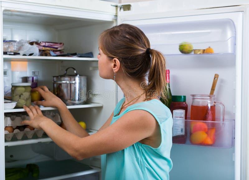 Donna vicino al frigorifero pieno fotografia stock