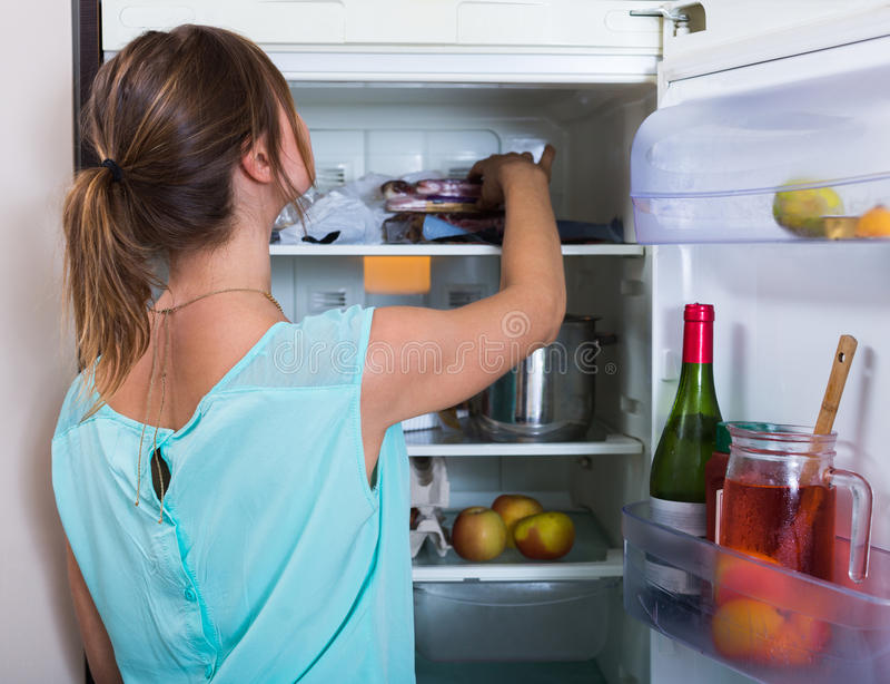 Donna vicino al frigorifero pieno immagine stock libera da diritti