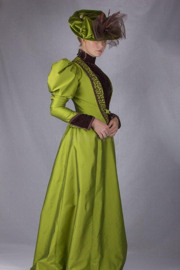 Donna vittoriana recente in insieme di seta verde immagine stock