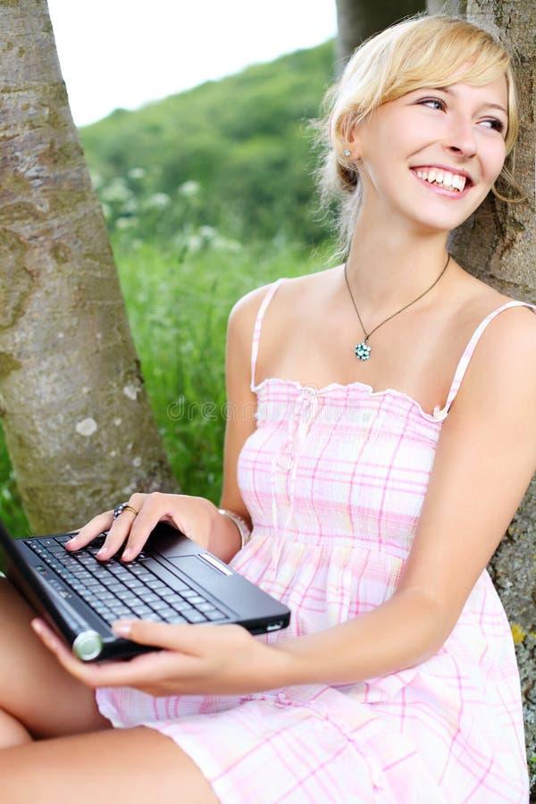 Donna vivace che utilizza il suo computer portatile nella natura immagini stock libere da diritti