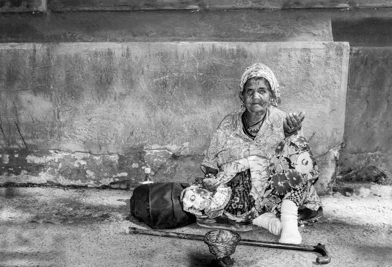 Donna zingaresca senza tetto anziana del mendicante con la pelle corrugata del fronte che elemosina i soldi sulla via nella città fotografie stock