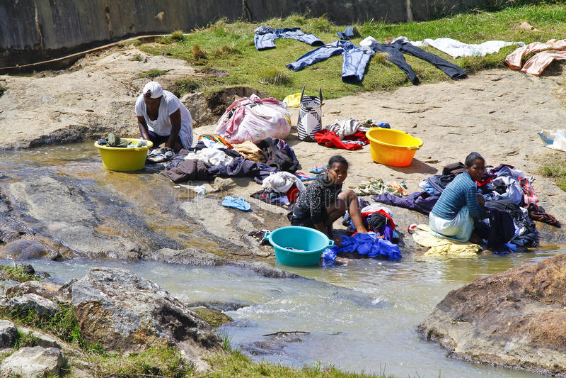 Donne africane che lavano i vestiti su un fiume I vestiti lavati sono bugia fotografia stock libera da diritti