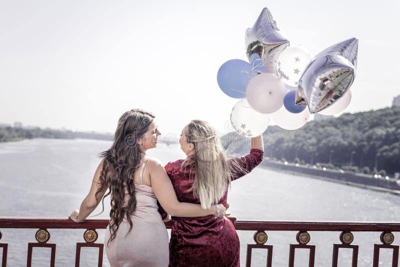 Donne alla moda allegre positive che si abbracciano fotografia stock