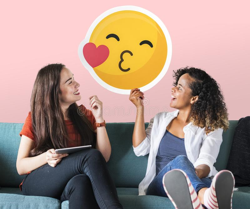 Donne allegre che tengono un'icona baciante dell'emoticon fotografie stock libere da diritti
