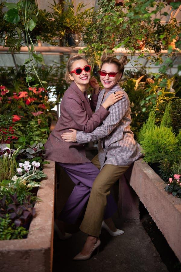 Donne allegre positive che si abbracciano fotografia stock