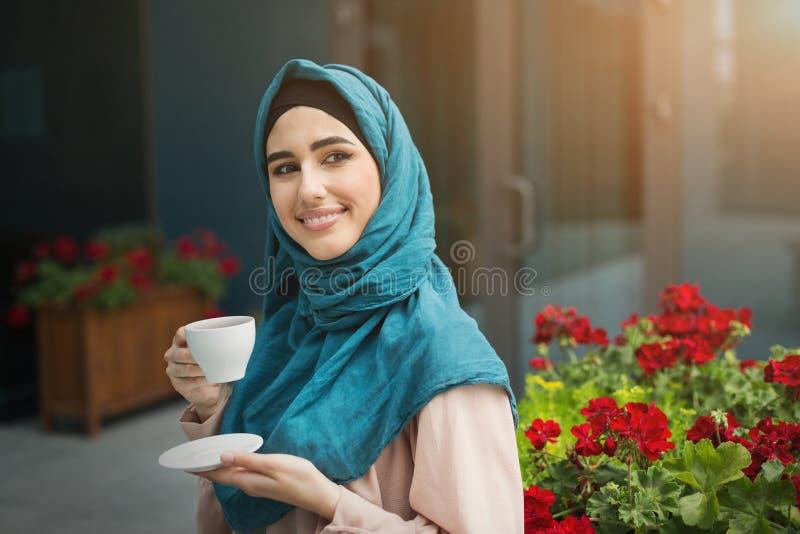 Donne arabe in caffè bevente del hijab all'aperto fotografie stock